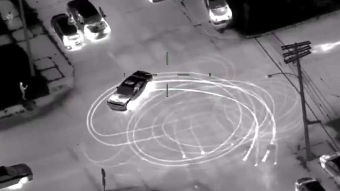 Ein Dodge Challenger brennt Donuts auf einer Kreuzung, Aufnahmen einer Nachtsichtkamera