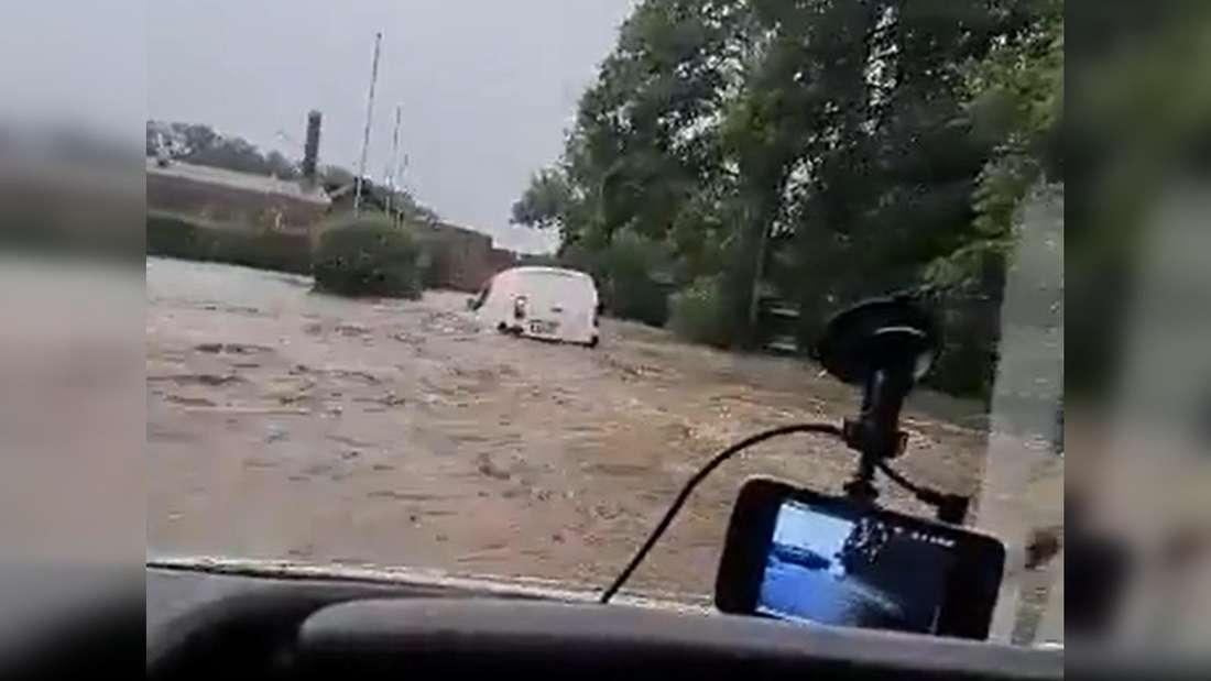 Blick durch Windschutzscheibe: weißer Lieferwagen im Hochwasser
