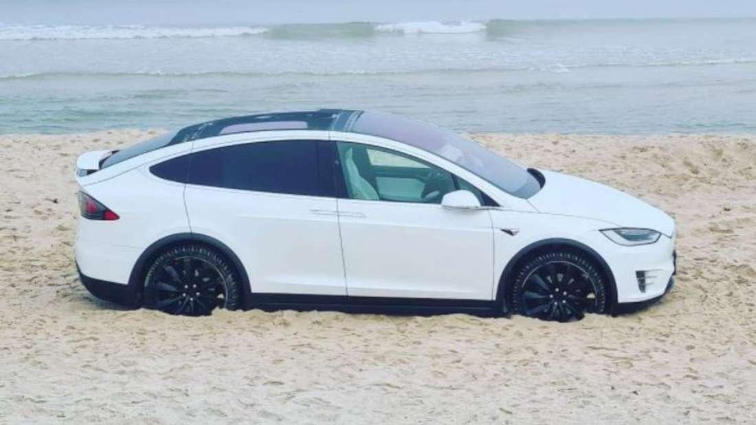 Ein weißes Tesla Model X bleibt im Sand am Strand von Kampen stecken.