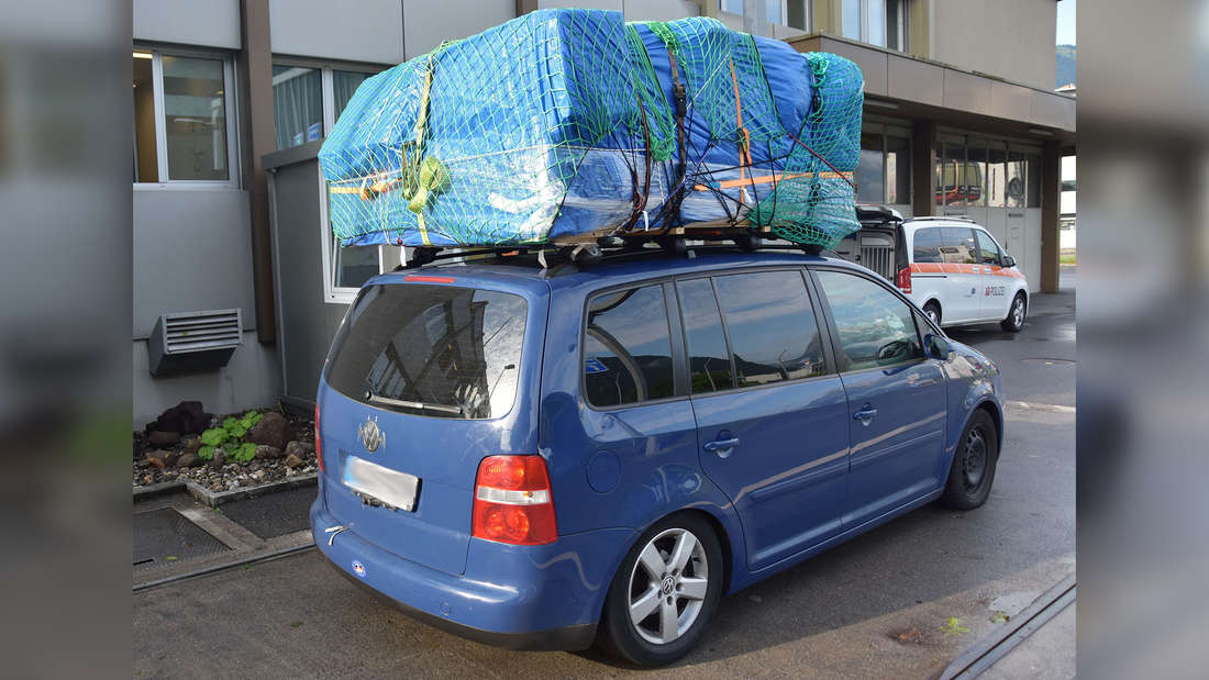 Ein blauer VW Touran ist auf dem Autodach überladen.
