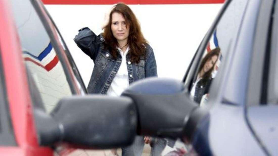 Frau steht hinter zwei zugeparkten Autos. (Symbolbild)