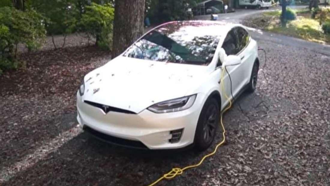 Ein weißes Tesla Model X lädt über ein Ladekabel an einer Haushaltssteckdose.