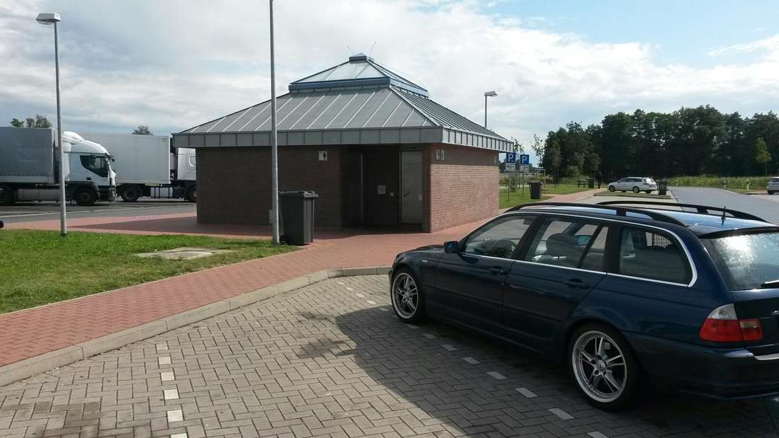 Ein BMW parkt vor einem Toilettenhäuschen an der Autobahn. (Symbolbild)