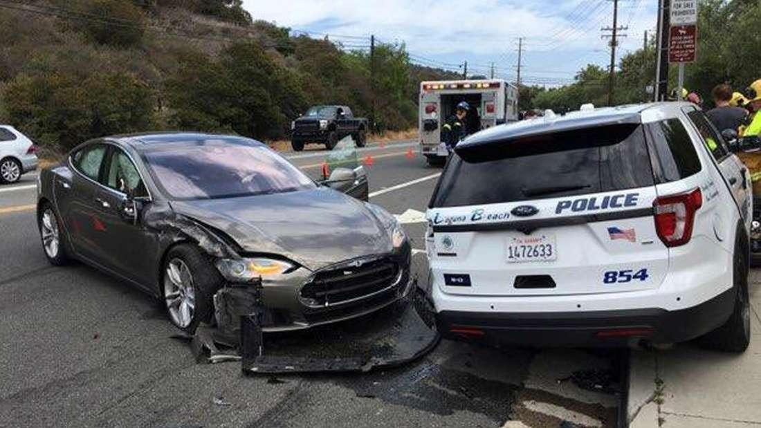 Ein verunfalltes Tesla Model S neben einem Polizeifahrzeug