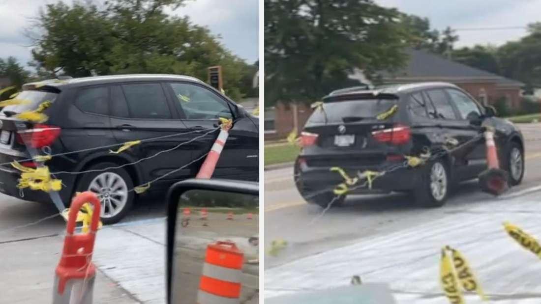 EIn BMW X3 fährt durch eine Baustelle und schleift Pylonen mit.
