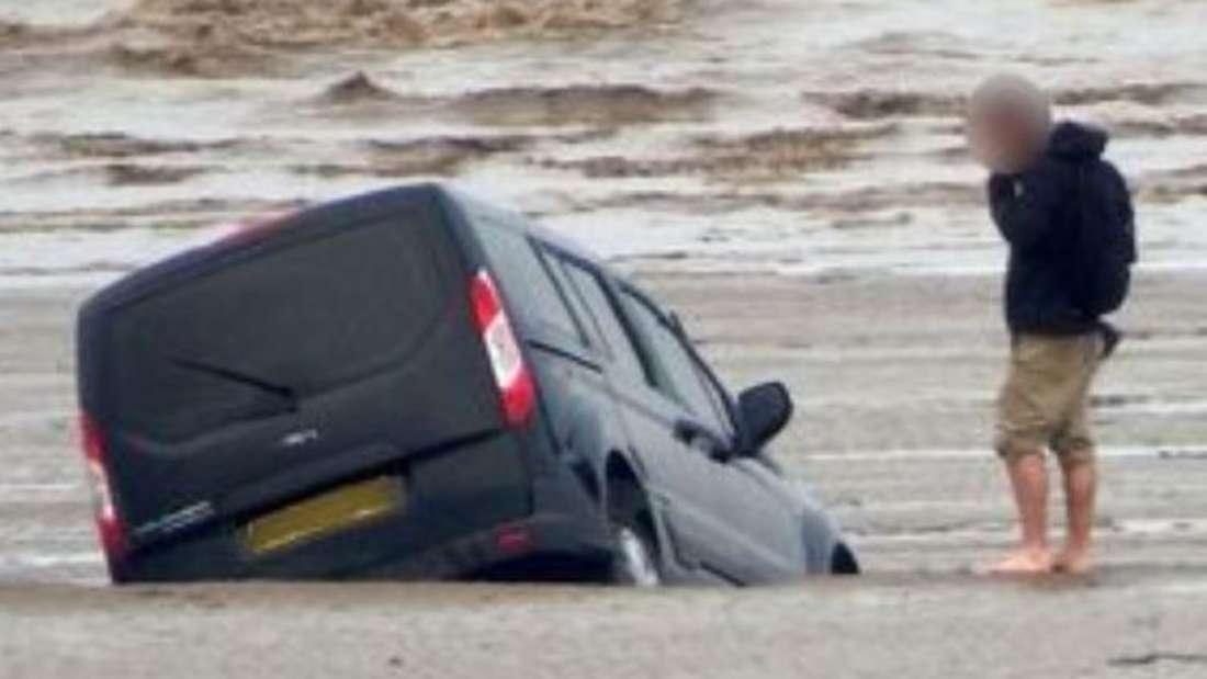 Der Ford Tourneo Connect versinkt in schlammigem Sand, sein Besitzer sieht hilflos dabei zu.