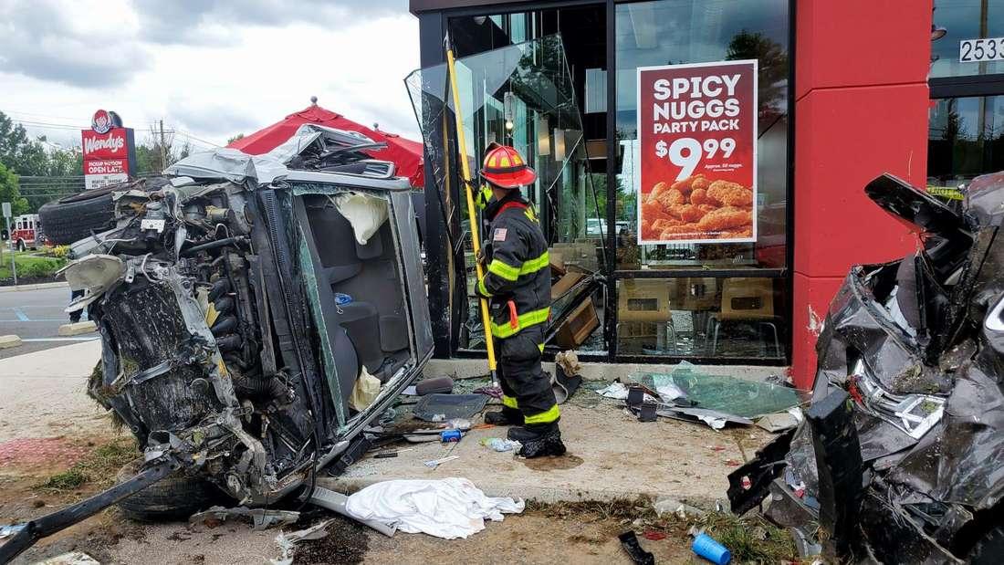 Ein zerstörter Toyota Corolla liegt vor dem demolierten Fast-Food-Restaurant, daneben steht ein Feuerwehrmann.