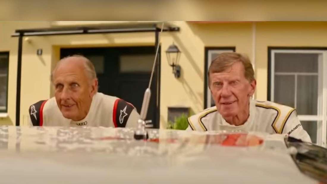 Hans-Joachim Stuck und Walter Röhrl schauen hinter einem Auto hervor.