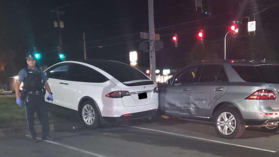 Ein Tesla Model X steht auf einem Grünstreifen, daneben ein beschädigter Mercedes ML und ein Polizist