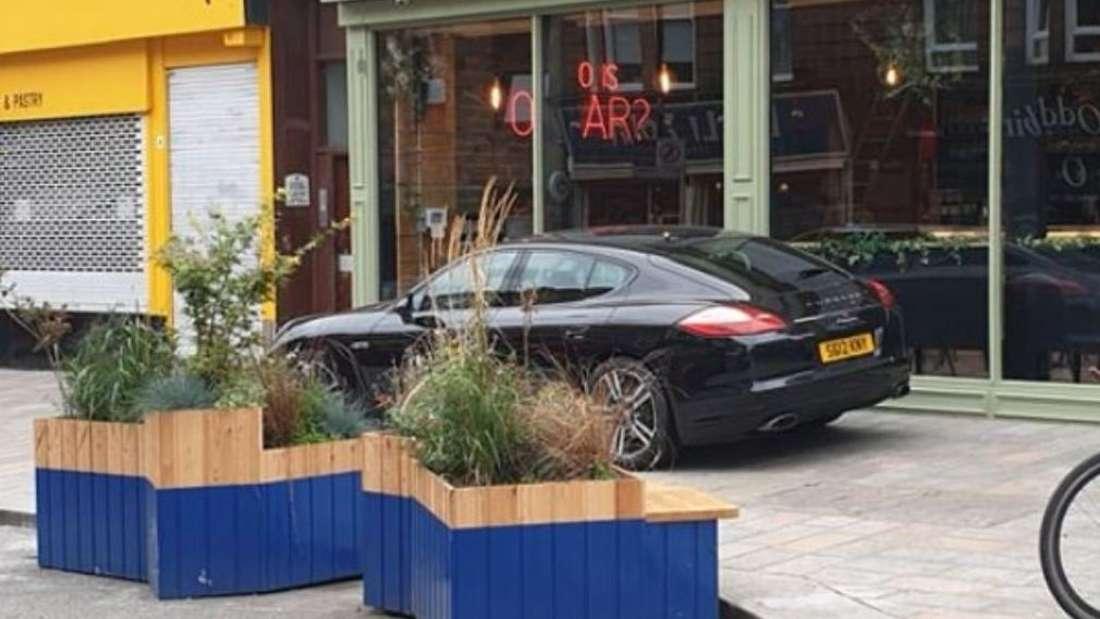 Ein schwarzer Porsche Panamera steht vor einer Bar auf dem Bürgersteig.
