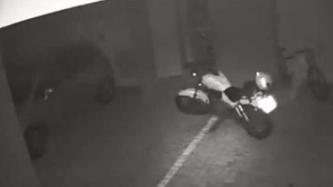 Ein Motorrad fährt von selbst durch eine Tiefgarage, eine Überwachungskamera filmt alles.