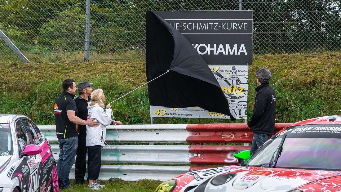 """Familienangehörige der verstorbenen Rennfahrerin enthüllen das Schild der """"Sabine-Schmitz-Kurve"""" auf der Nordschleife."""
