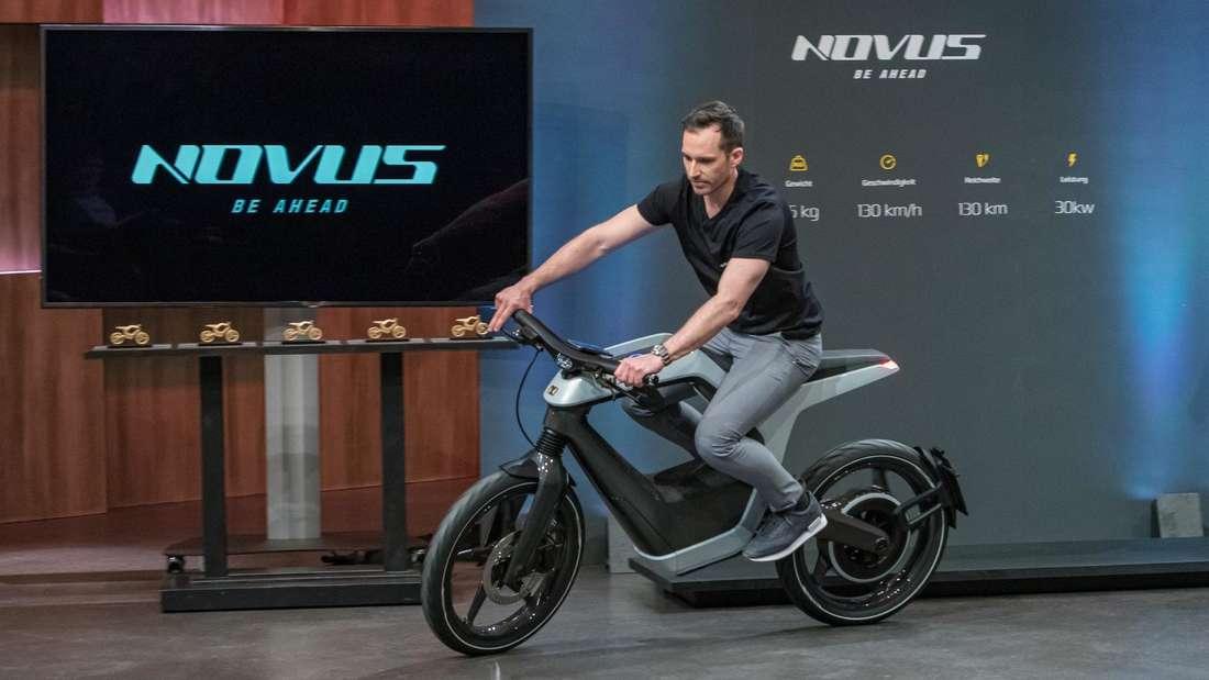 Ein Mann fährt auf einem Novus-Elektro-Motorrad.