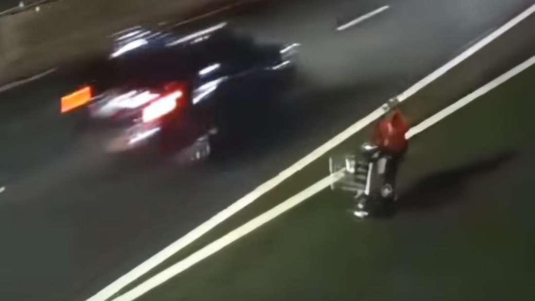 Eine Person mit einem motorisierten Einkaufswagen fährt auf einer Autobahn.