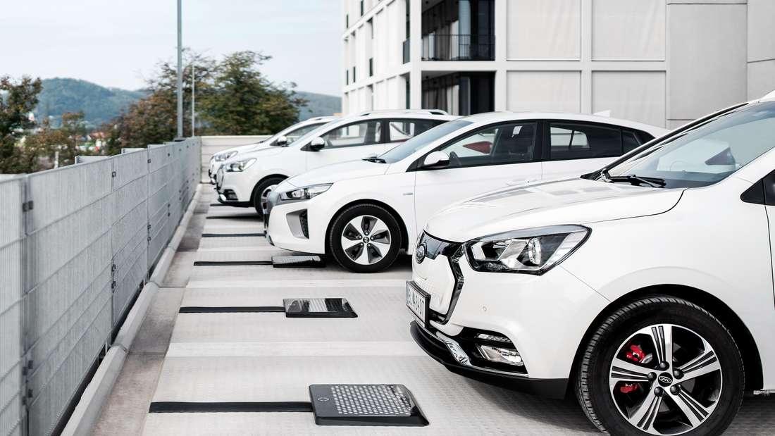 Mehrere Elektroautos stehen nebeneinander in Parkbuchten mit Ladepads.