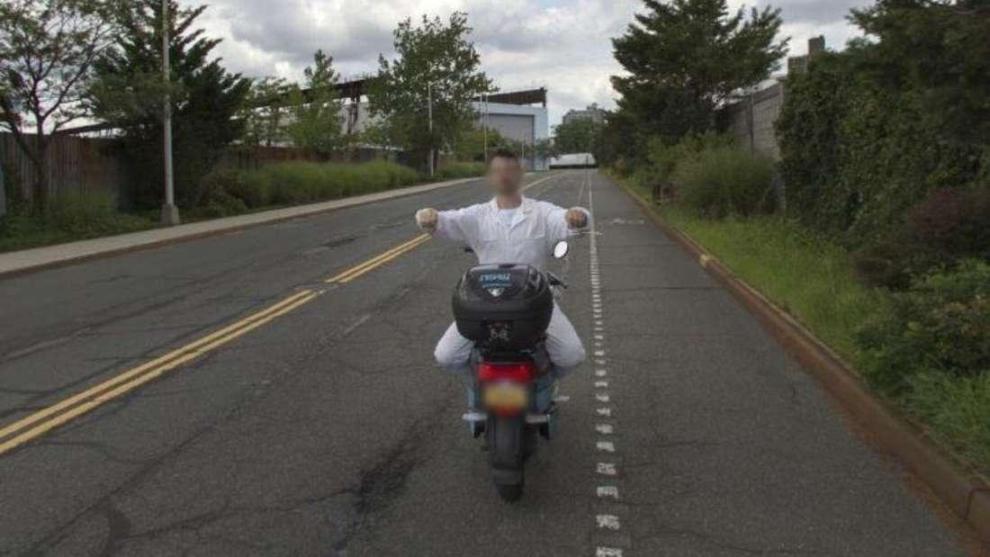 Ein Mann im weißen Overall fährt verkehrt herum auf einem Motorrad.