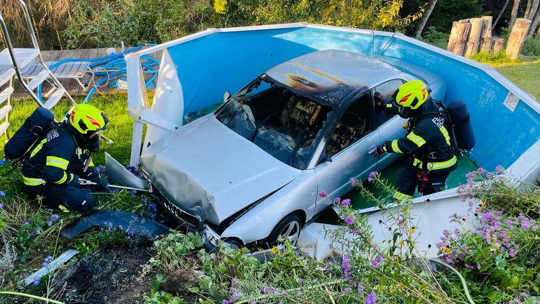 Zwei Feuerwehrleute hantieren an einem ausgebrannten Audi A4, der in einem Pool steht.