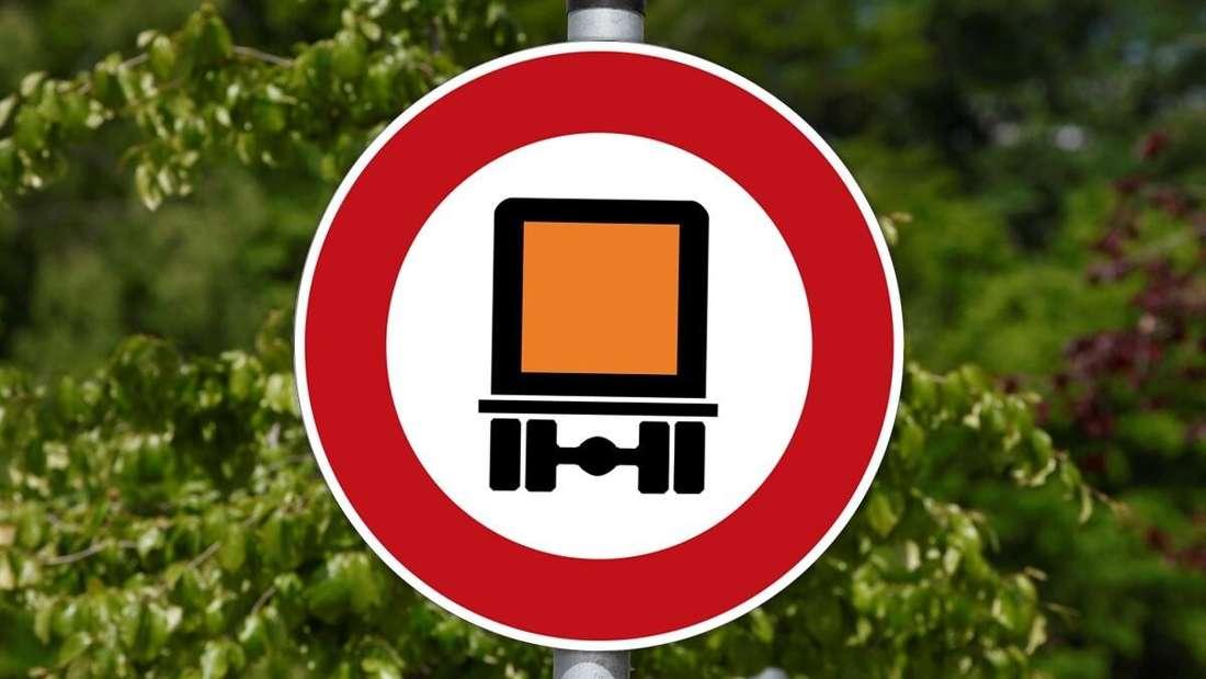 Ein Schild, das die Durchfahrt von Gefahrgut-Transportern verbietet. (Montage)