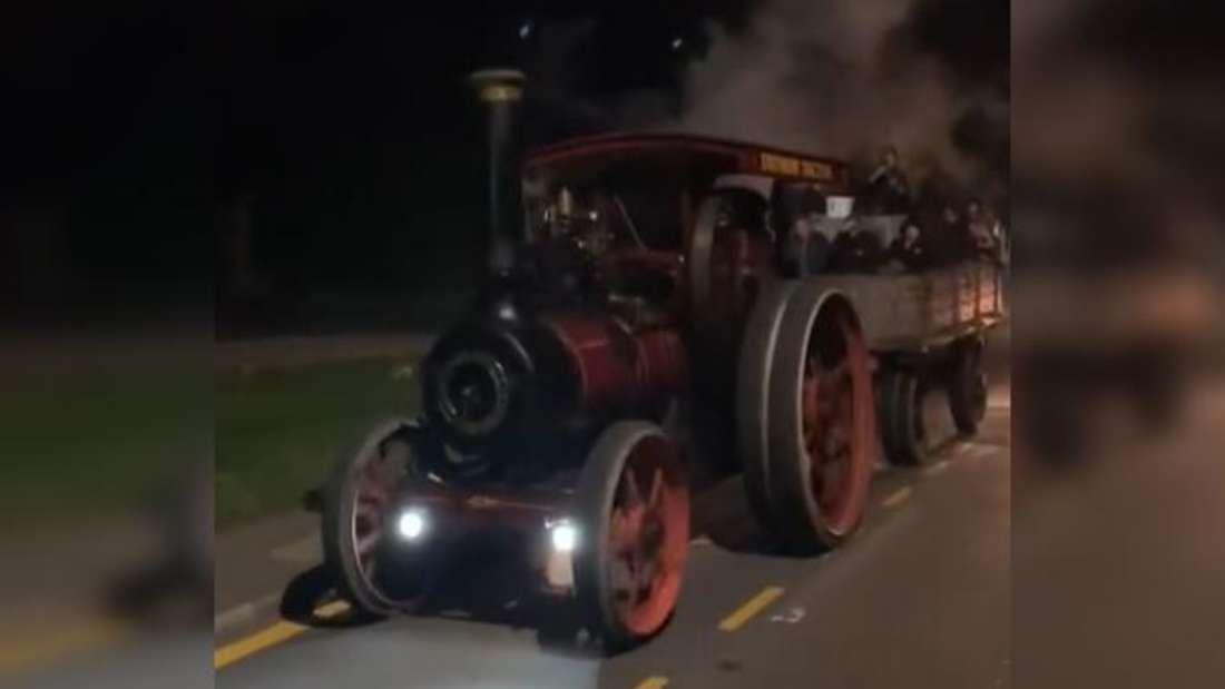 Eine Dampfmaschine fährt nachts auf einer Straße.