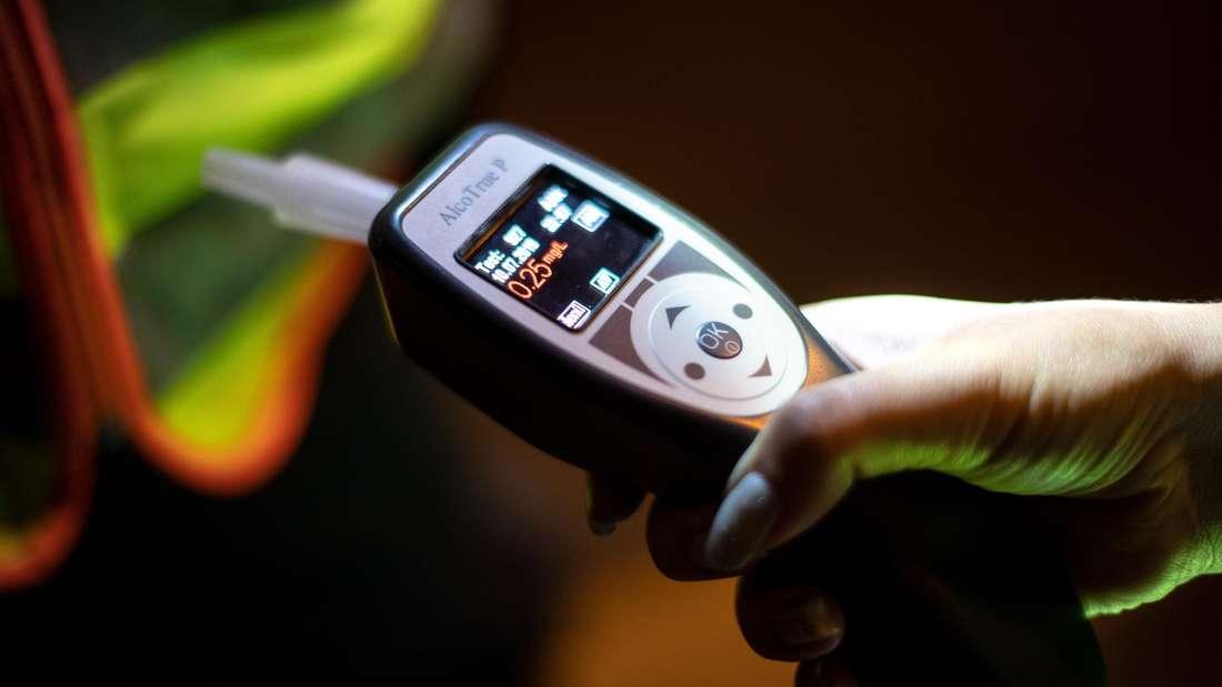 Eine Polizistin kontrolliert mit einem Atemalkoholtest einen Verkehrsteilnehmer. (Symbolbild)