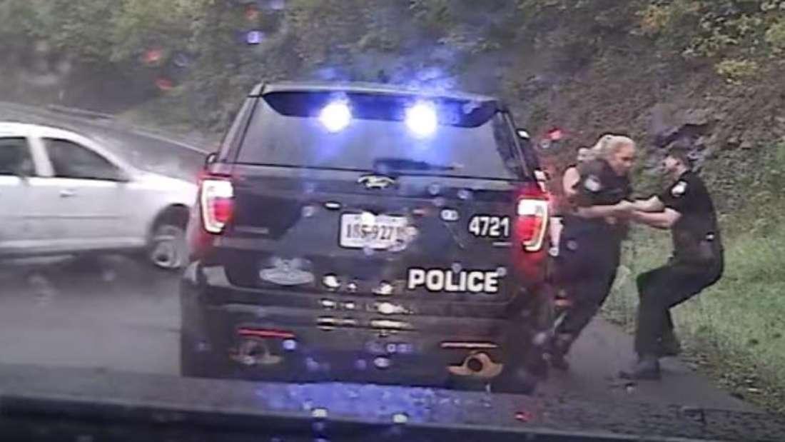 Ein Polizist bringt seine Kollegin in Sicherheit.