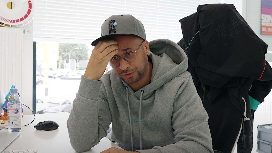 JP Kraemer sitzt an seinem Schreibtisch und greift mit der Hand an seine Stirn.